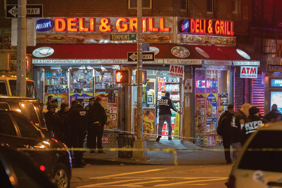 Investigators work in the area where two NYPD officers were shot in the Bedford-Stuyvesant neighborhood of the Brooklyn borough of New York on Saturday, Dec. 20, 2014. Police said an armed man walked up to two officers sitting inside a patrol car and opened fire before running into a nearby subway station and committing suicide. Both police officers were killed. (AP Photo/John Minchillo)