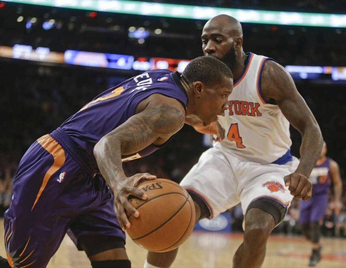 Phoenix Suns' Eric Bledsoe (2) drives past New York Knicks' Quincy Acy (4) during the first half of an NBA basketball game Saturday, Dec. 20, 2014, in New York. (AP Photo/Frank Franklin II)