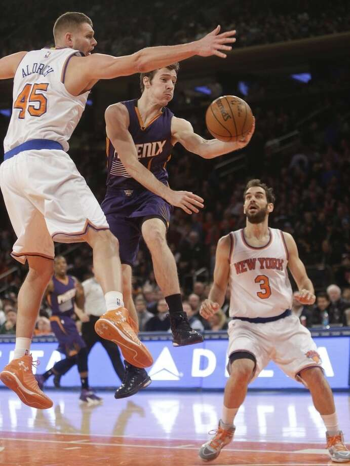 Phoenix Suns' Goran Dragic (1), of Slovenia, passes away from New York Knicks' Cole Aldrich (45) and Jose Calderon (3), of Spain, during the first half of an NBA basketball game Saturday, Dec. 20, 2014, in New York. (AP Photo/Frank Franklin II)