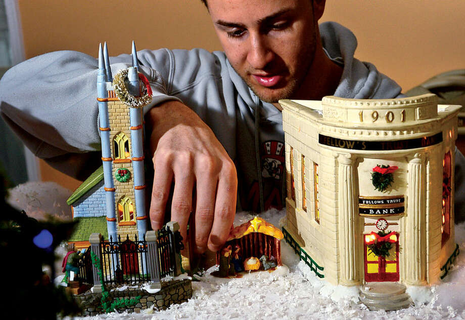 Hour photo / Erik Trautmann Norwalk resident Pat Scarpone's grandson, Anthony Daniello, has been the recent chief architect in constructing an elaborate model Christmas Village which the family has built every year for the past 25 years .