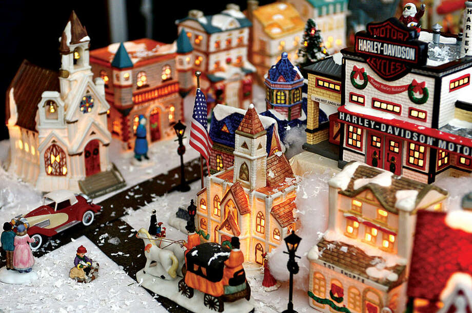 Hour photo / Erik Trautmann Norwalk resident, 80-year-old Pat Scarpone, his wife Diane, and their extended family have constructed an elaborate model Christmas Village in their home every year for the past 25 years .