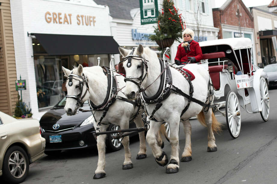 Hour photo/Chris Palermo. Beth Podnajecki of Loon Meadow Farm of Norfolk, CT gives horse and buggy rides on Main Street in Westport Sunday morning. The Westport Downtown Merchants Association celebrated the season with downtown holiday entertainment for the community.