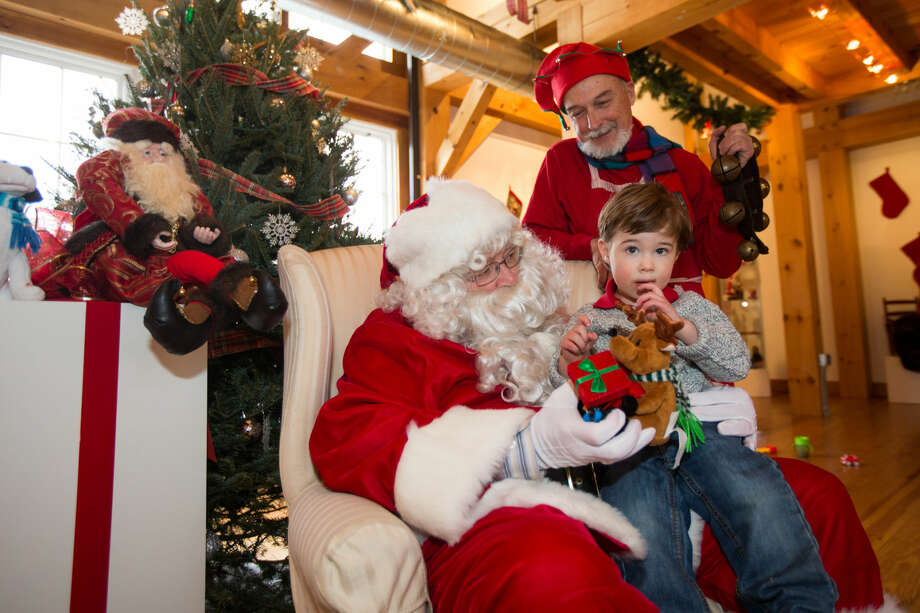 Hour photo/Chris Palermo. Grant Failla, 2, sits with Santa and one of his elves at the Weston Historical Society Sunday afternoon.