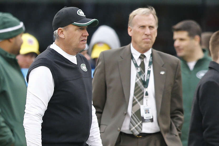 New York Jets head coach Rex Ryan, left, and general manager John Idzik watch their team warm up before and NFL football game against the New England Patriots, Sunday, Dec. 21, 2014, in East Rutherford, N.J. (AP Photo/Julio Cortez)