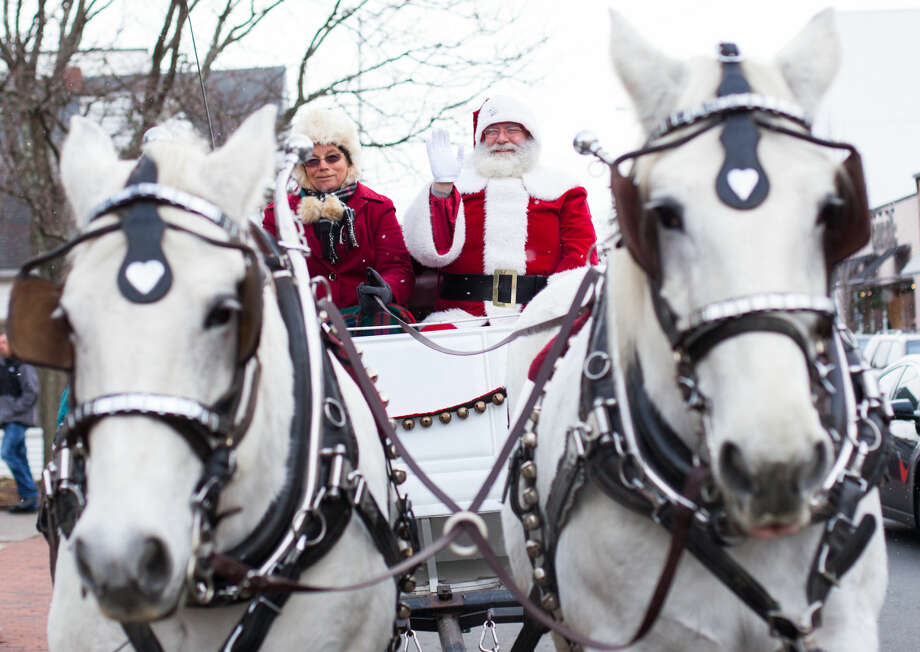 Hour photo/Chris Palermo. Santa takes a ride on the horse and buggy with Beth Podnajecki on Main Street in Westport Sunday morning. The Westport Downtown Merchants Association celebrated the season with downtown holiday entertainment for the community.