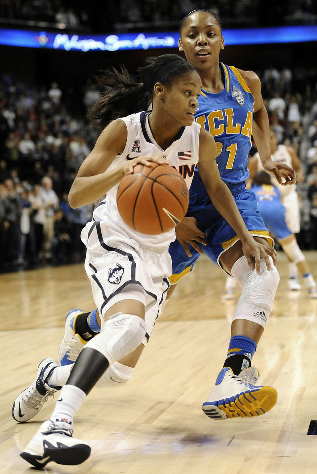 Connecticut's Moriah Jefferson, left, drives around UCLA's Nirra Fields, right, during the first half of an NCAA college basketball game, Sunday, Dec. 21, 2014, in Uncasville, Conn. (AP Photo/Jessica Hill)