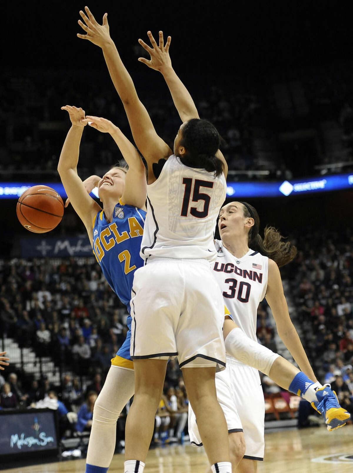 Connecticut's Breanna Stewart, back right, and Gabby Williams, front, force the ball from UCLA's Kari Korver during the first half of an NCAA college basketball game, Sunday, Dec. 21, 2014, in Uncasville, Conn. (AP Photo/Jessica Hill)