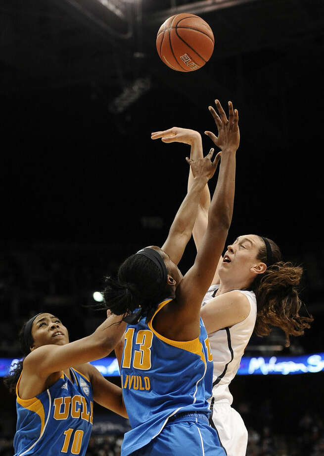 Connecticut's Breanna Stewart, right, shoots over UCLA's Kacy Swain, left, and Luiana Livulo, center, during the second half of an NCAA college basketball game, Sunday, Dec. 21, 2014, in Uncasville, Conn. Connecticut won 86-50. (AP Photo/Jessica Hill)