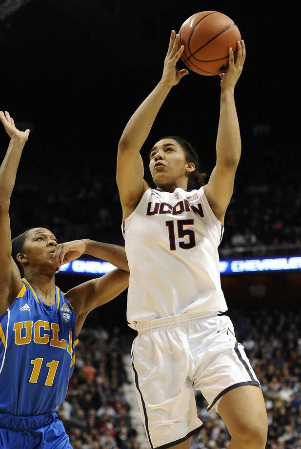 Connecticut's Gabby Williams, right, shoots over UCLA's Lajahna Drummer during the second half of an NCAA college basketball game, Sunday, Dec. 21, 2014, in Uncasville, Conn. Connecticut won 86-50. (AP Photo/Jessica Hill)