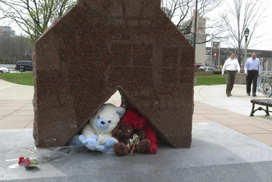 FILE - In this May 8, 2014 file photo, flowers and stuffed animals form a makeshift memorial in a Milwaukee park where a white Milwaukee police officer shot and killed a black man. Prosecutors said Monday, Dec. 22, 2014, that Christopher Manney won't face criminal charges because he shot Dontre Hamilton in self-defense. (AP Photo/Dinesh Ramde, File)