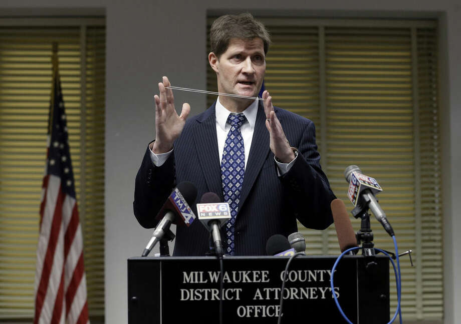 Milwaukee County District Attorney John Chisholm demonstrates bullet trajectory at news conference Monday, Dec. 22, 2014, in Milwaukee. Chisholm announced that there would be no charges against former police office Christopher Manney in the fatal shooting of Dontre Hamilton. (AP Photo/Morry Gash)