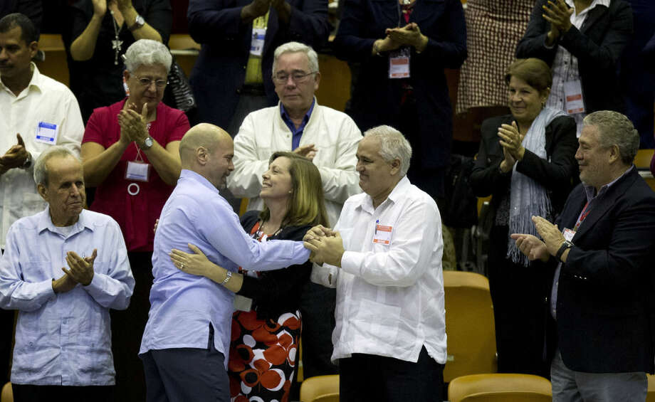 """In this Dec. 20, 2014 photo, Cuba's head of North American affairs, Josefina Vidal, front row center, embraces Gerardo Hernandez, member of """"The Cuban Five,"""" at the closing from a twice-annual legislative session at the National Assembly in Havana. In the country's first detailed public response to Obama's historic announcement last week,Vidal said that Cuba welcomes """"the entire package"""" offered by Obama. That includes U.S. equipment to improve the Cuban internet and potentially unlimited exports of Cuba's new class of private business owners. (AP Photo/Ramon Espinosa)"""