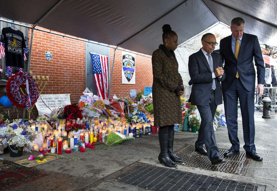 From left, New York City first lady Chirlane McCray, Pastor Michael Durso, and New York City Mayor Bill de Blasio walk form a makeshift memorial after laying a bouquet, Tuesday, Dec. 23, 2014, near the site where New York Police Department officers Rafael Ramos and Wenjian Liu were murdered in the Brooklyn borough of New York. Police say Ismaaiyl Brinsley ambushed the two officers in their patrol car in broad daylight Saturday, fatally shooting them before killing himself inside a subway station. (AP Photo/Craig Ruttle)