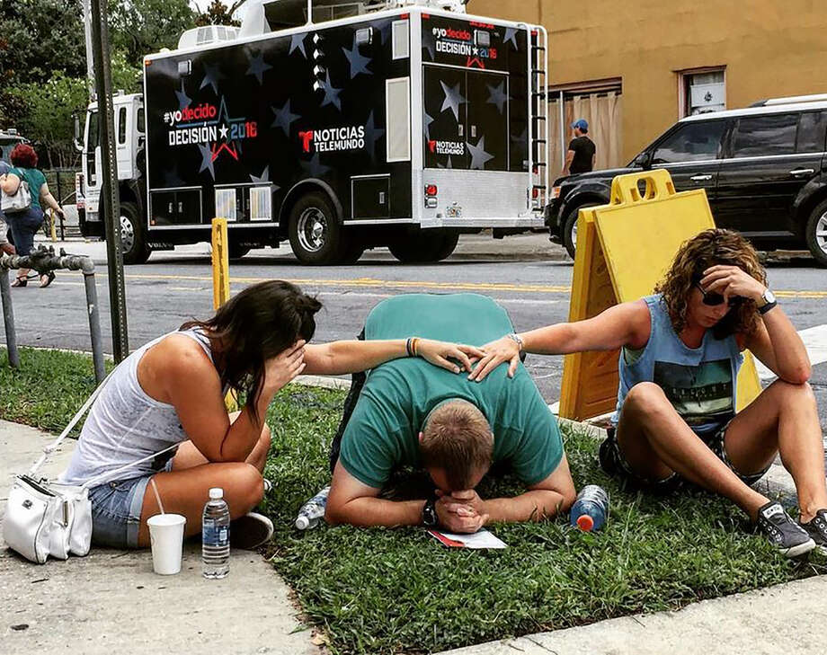 """TOPSHOT - In this photo courtesy of the Instagram site of the_pixel_trappa, shows people mourning for victims of the mass shooting near the Pulse gay nightclub in Orlando, Florida, on June 12, 2016.  Fifty people died and another 53 were injured when a gunman opened fire and seized hostages at a gay nightclub in Florida, police said June 12, making it the worst mass shooting in US history. / AFP PHOTO / the_pixel_trappa / Handout / RESTRICTED TO EDITORIAL USE - MANDATORY CREDIT """"AFP PHOTO / INSTAGRAM/the_pixel_trappa"""" - NO MARKETING - NO ADVERTISING CAMPAIGNS - DISTRIBUTED AS A SERVICE TO CLIENTS  HANDOUT/AFP/Getty Images Photo: HANDOUT, AFP/Getty Images / AFP"""