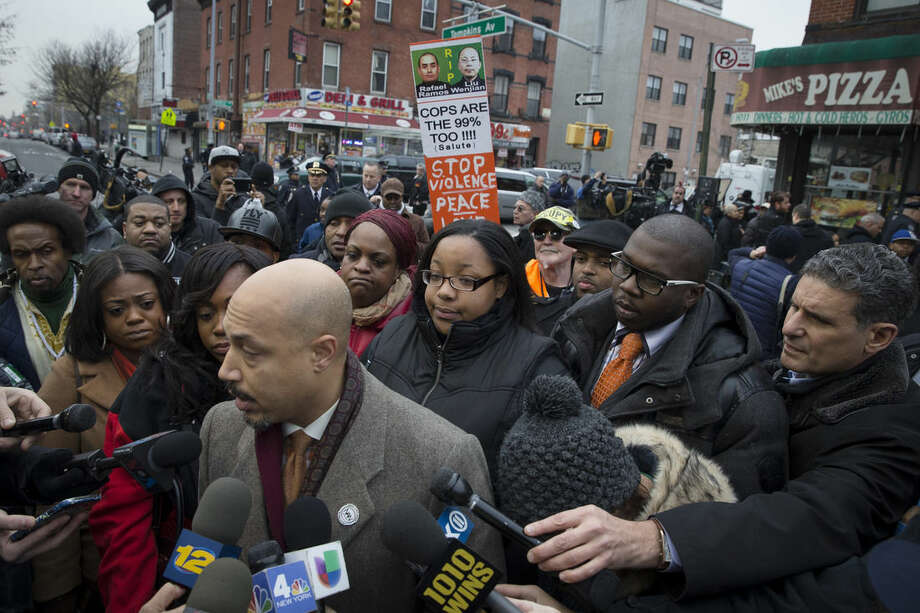 Emerald Garner, daughter of Eric Garner, center, stands with National Action Network members near a makeshift memorial, Monday, Dec. 22, 2014, at the site where New York Police Department officers Rafael Ramos and Wenjian Liu were murdered in the Brooklyn borough of New York. Police say Ismaaiyl Brinsley ambushed the two officers in their patrol car in broad daylight Saturday, fatally shooting them before killing himself inside a subway station. (AP Photo/Seth Wenig)