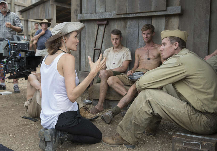 "In this image released by Universal Pictures, director Angelina Jolie, left, speaks with Garrett Hedlund on the set of ""Unbroken."" (AP Photo/Universal Pictures, David James)"
