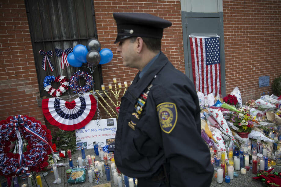 A member of the New Rochelle, N.Y., police department visits a makeshift memorial, on Monday, Dec. 22, 2014, near the site where New York Police Department officers Rafael Ramos and Wenjian Liu were murdered in the Brooklyn borough of New York. Police say Ismaaiyl Brinsley ambushed the two officers in their patrol car in broad daylight Saturday, fatally shooting them before killing himself inside a subway station. (AP Photo/Seth Wenig)