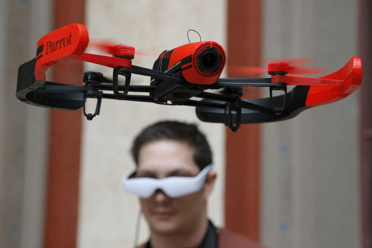 FILE - In this Nov. 7, 2014 file photo, pilot Maxime Tran Quan Tien guides his Parrot Bebop drone during a presentation to the press in Paris. Drones _ the remotely controlled flying devices that often carry cameras and can be navigated with a smartphone or controller _ are