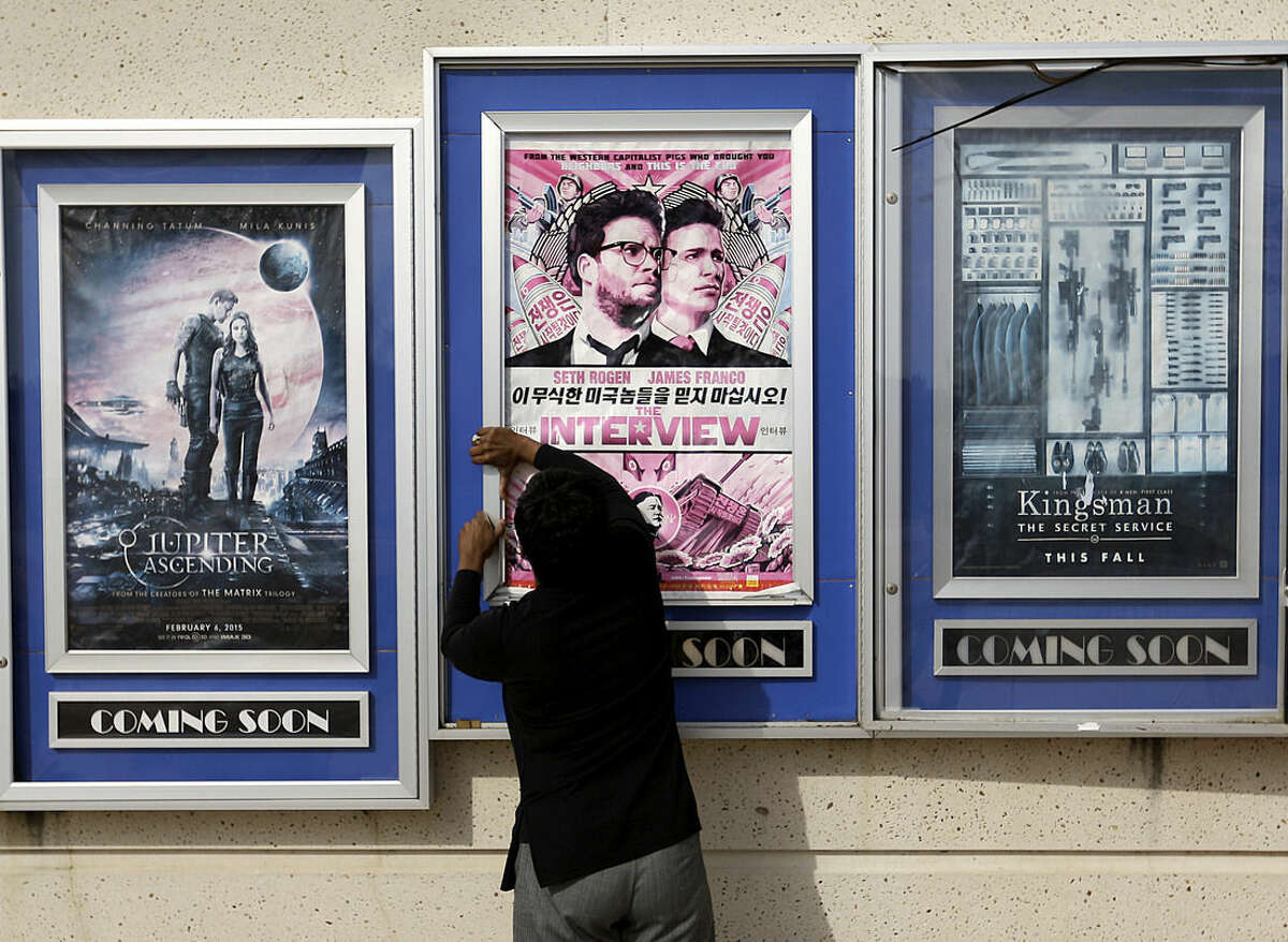 FILE - In this Wednesday, Dec. 17, 2014 file photo, a worker removes poster for the movie