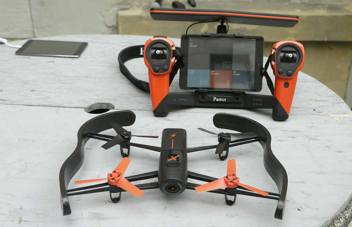 FILE - This May 8, 2014 file photo shows a Parrot Bebop drone, foreground, and the Skycontroller, at a Parrot event in San Francisco. Drones _ the remotely controlled flying devices that often carry cameras and can be navigated with a smartphone or controller _ are