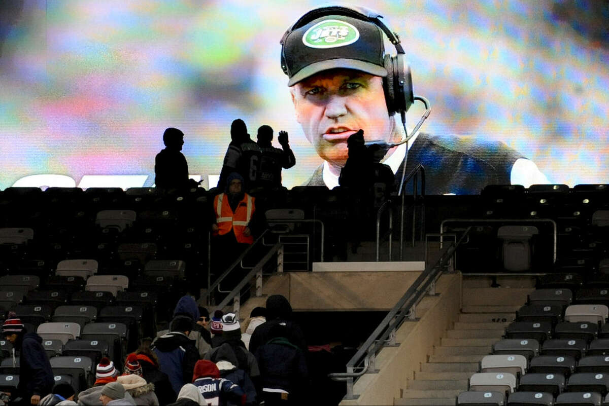 Fans leave MetLife Stadium as New York Jets head coach Rex Ryan is shown on a screen after an NFL football game against the New England Patriots, Sunday, Dec. 21, 2014, in East Rutherford, N.J. The Patriots won 17-16. (AP Photo/Bill Kostroun)