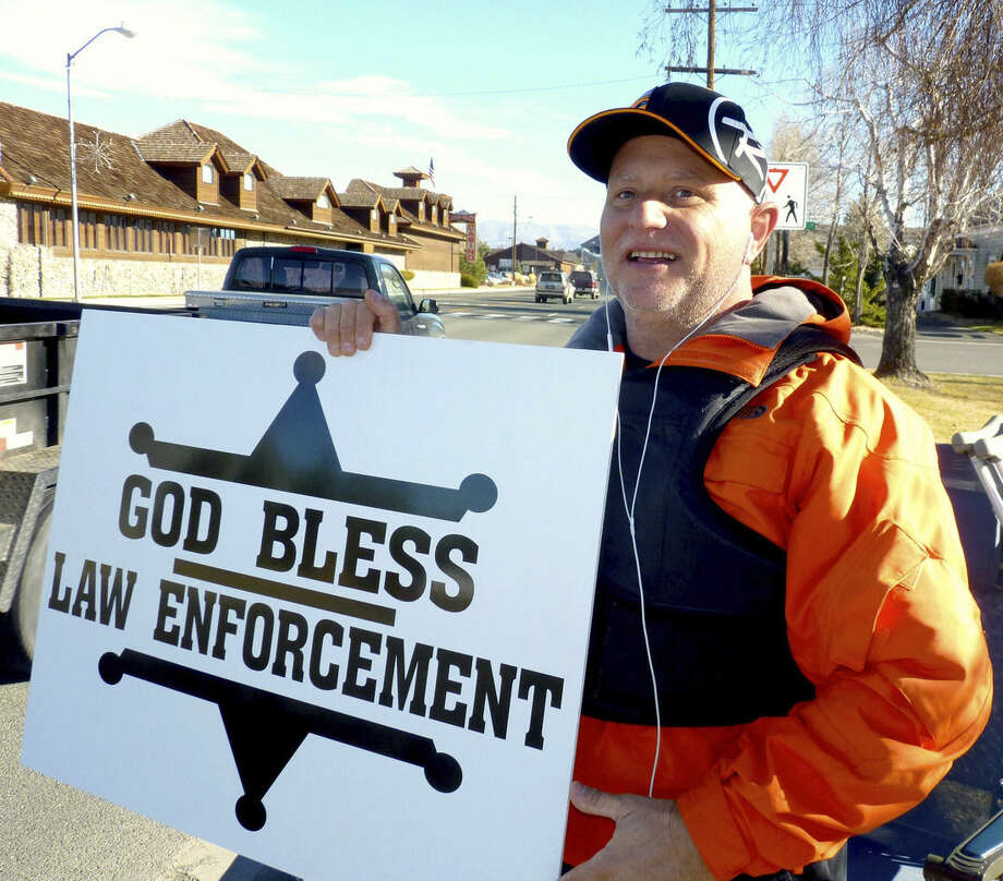"""In this photo taken on Monday, Dec. 22, 2014, passing motorists honk as retired Douglas County sheriff's deputy John Munk of Gardnerville, Nev., holds a sign showing his support for law enforcement, in front of the Minden Post Office south of Carson City. """" It's disheartening how people are treating law enforcement across the country,'' said Munk, who retired in 2012 after more than 20 years on the force. (AP Photo/The Record Courier, Kurt Hildebrand)"""