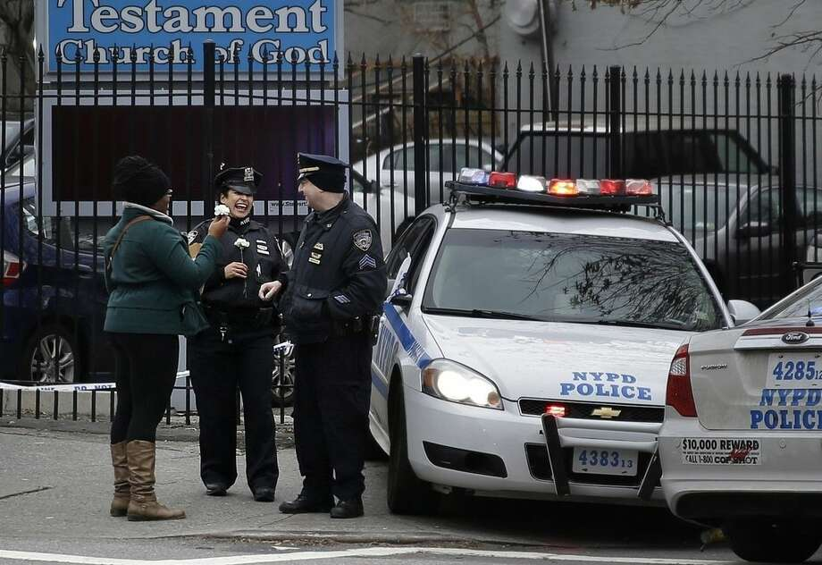 In this Dec. 21, 2014 photo, a women gives flowers to police officers who watch over a corner where two police officers were killed in the Brooklyn borough of New York. At a time when many in the nation's police community feel embattled, Americans in cities and towns across the country are making an effort to express support and gratitude. (AP Photo/Seth Wenig)