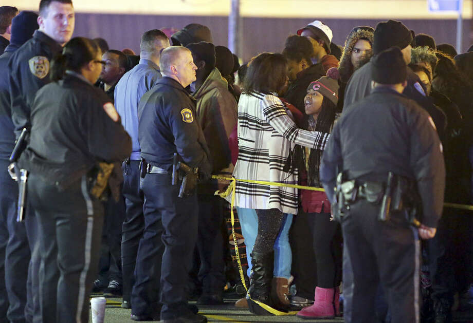 Police hold back a crowd at the perimeter of a scene on Wednesday, Dec. 24, 2014, following a shooting Tuesday at a gas station in Berkeley, Mo. St. Louis County police say a man who pulled a gun and pointed it at an officer has been killed. (AP Photo/St. Louis Post-Dispatch, David Carson)