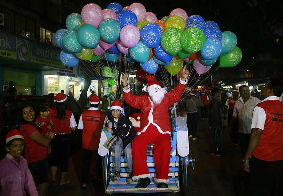 A man dressed as Santa Claus sits on a horse cart with a child during a Christmas carnival in Mumbai, India, Tuesday, Dec 23, 2014. (AP Photo/Rafiq Maqbool)--
