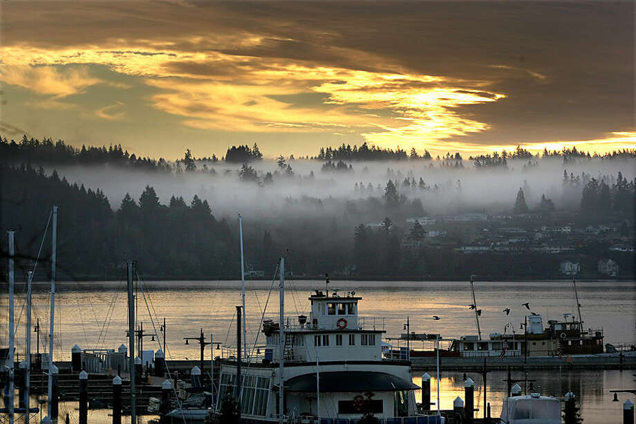 Low clouds hover in the trees in Port Orchard as photographed from the Bremerton Harborside Marina in Bremerton, Wash., Monday, Dec. 22, 2014. (AP Photo/Kitsap Sun, Larry Steagall)