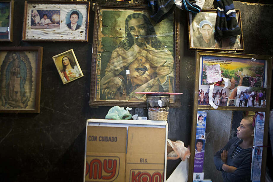 """In this Thursday, Nov. 27, 2014 photo, Roberto Castellanos is reflected in a mirror at his home in Tegucigalpa, Honduras. """"Here, every day that passes is another day I'm alive,"""" Roberto said. His view is shaped by experience, having already seen five people murdered, and is shared by friends who wish they had Roberto's job to help support their families. The alternative, they say, is less food at home and an idleness that makes them easy prey for street gangs that control much of Tegucigalpa, the capital of Honduras. (AP Photo/Esteban Felix)"""