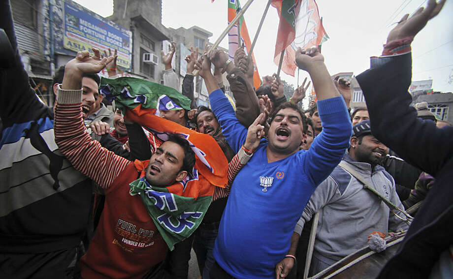 Bharatiya Janata Party (BJP) supporters dance to celebrate the news of early election result trends outside their party headquarters in Jammu, India, Tuesday, Dec. 23, 2014. India's ruling Hindu nationalist Bharatiya Janta Party is poised to emerge as an important political player in the disputed Himalayan region of Kashmir, as votes in local elections are being counted. (AP Photo/Channi Anand)