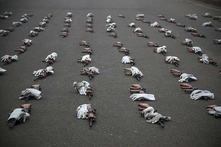 Guns and gloves of India's Air Force soldiers lie on a road during rehearsals for the upcoming Republic Day parade in New Delhi, India, Tuesday, Dec. 23, 2014. India marks Republic Day on Jan. 26 with military parades across the country. (AP Photo/Tsering Topgyal)