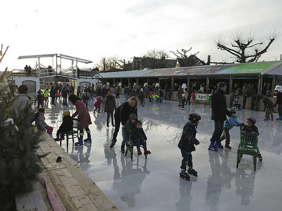 Children learn to skate using chairs as support, on the ice of a pond that serves as an ice rink in the winter months, outside the Rijksmuseum in Amsterdam, Tuesday, Dec. 23, 2014. (AP Photo/Margriet Faber)