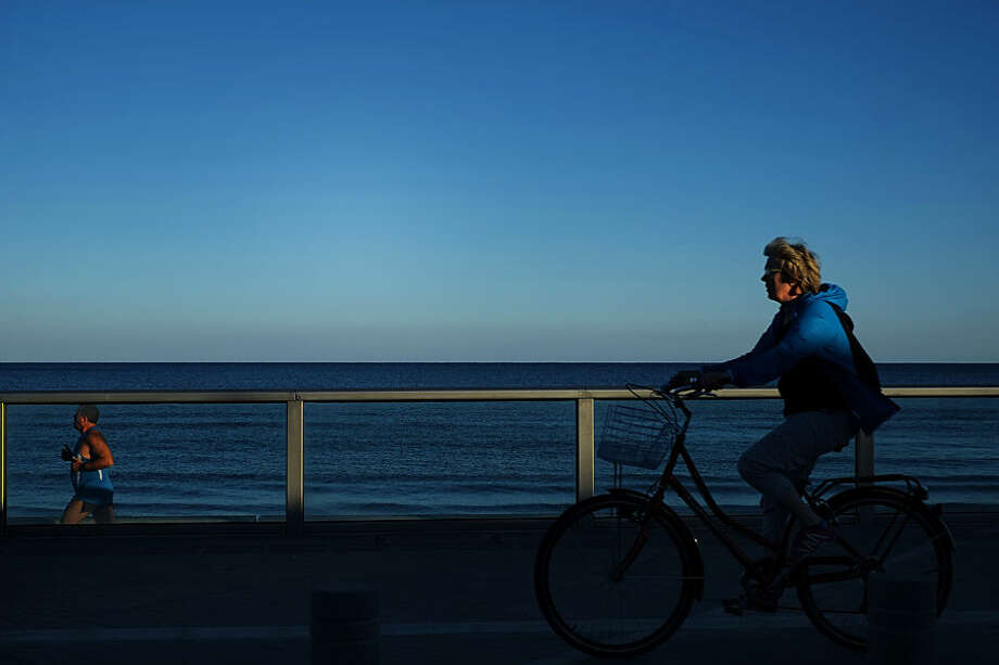 A man, left, runs as a woman cycles by the sea as they enjoy the good weather in southern costal city of Larnaca, Cyprus, Tuesday, Dec. 23, 2014. (AP Photo/Petros Karadjias)