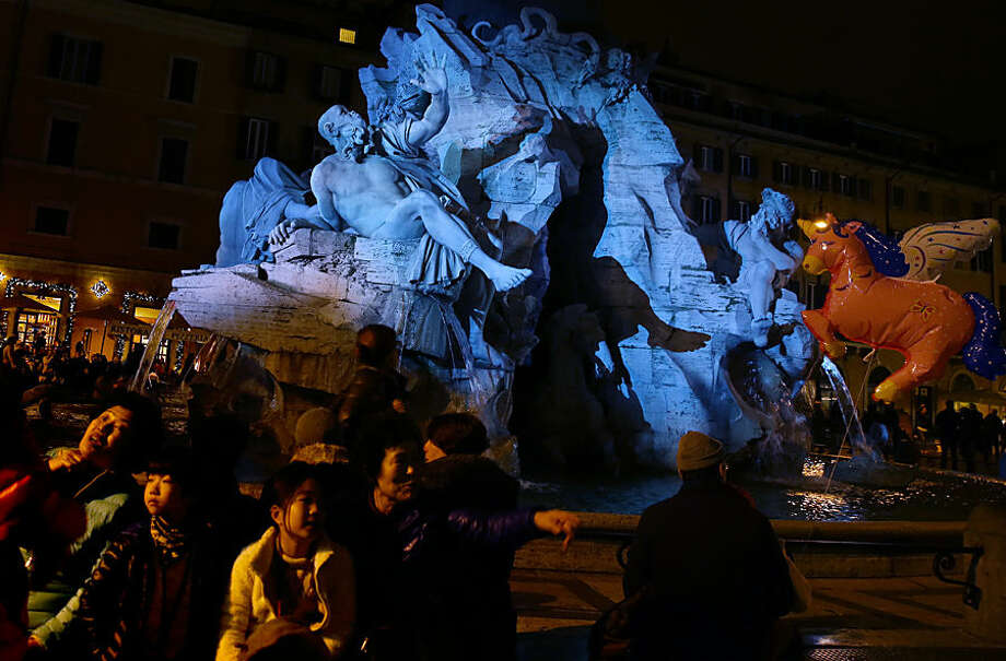 People and tourists sit and walk past the Italian sculptor Bernini's Four River fountain, lit up in colors, in Piazza Navona, Rome, Tuesday, Dec. 23, 2014. (AP Photo/Gregorio Borgia)