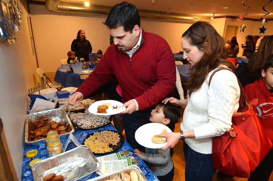 Zach and Jenn Schiller, with their 3-year-old son Luke ,sample some of the traditional food during the Wilton Community Hanukkah Party.
