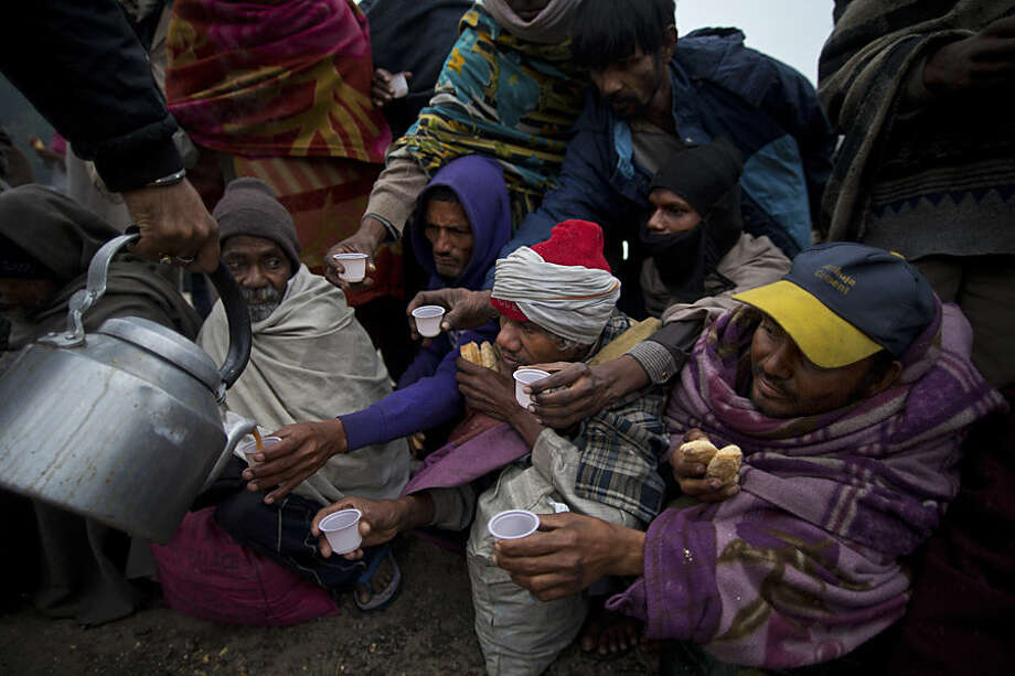 Homeless Indians receive tea and biscuits being served by a man on a chilly morning in New Delhi, India, Tuesday, Dec. 23, 2014. Intense cold coupled with a thick blanket of fog has engulfed most parts of north India throwing normal life out of gear and disrupting rail, road and air traffic. (AP Photo/Saurabh Das)