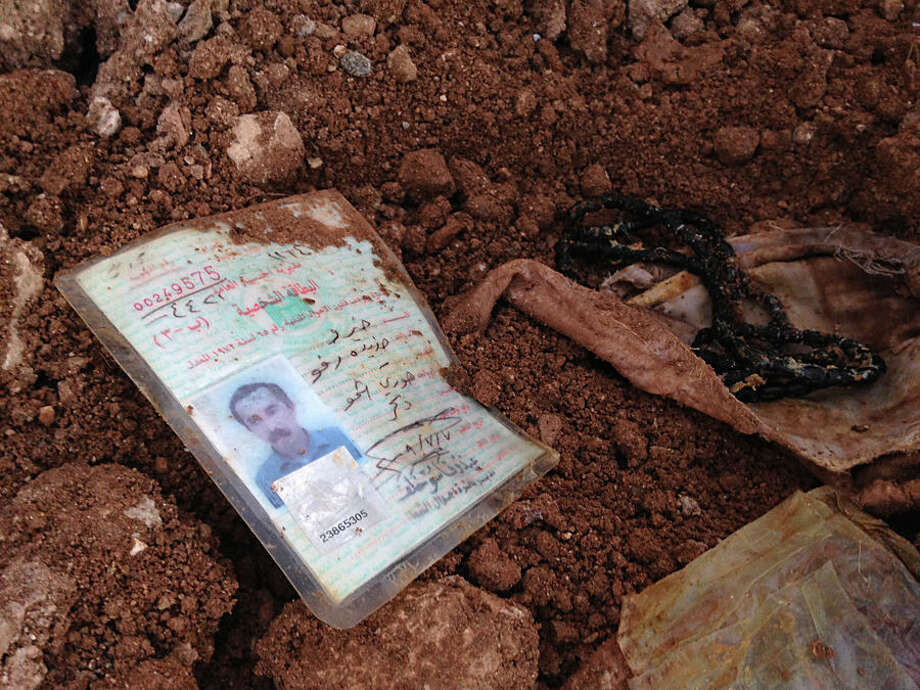 In this Monday, Dec. 22, 2014 photo, an identification card lies in the dirt in Hardan village in northern Iraq. A handful of Yazidis who fled this tiny northern Iraqi hamlet when Islamic State militants overran it in August have returned after Kurdish fighters drove out the extremists in recent days. They want to learn the fate of hundreds of missing relatives and neighbors and they fear they know where they are: Four mounds of freshly dug dirt in nearby fields they believe are graves. (AP Photo/Dalton Bennett)