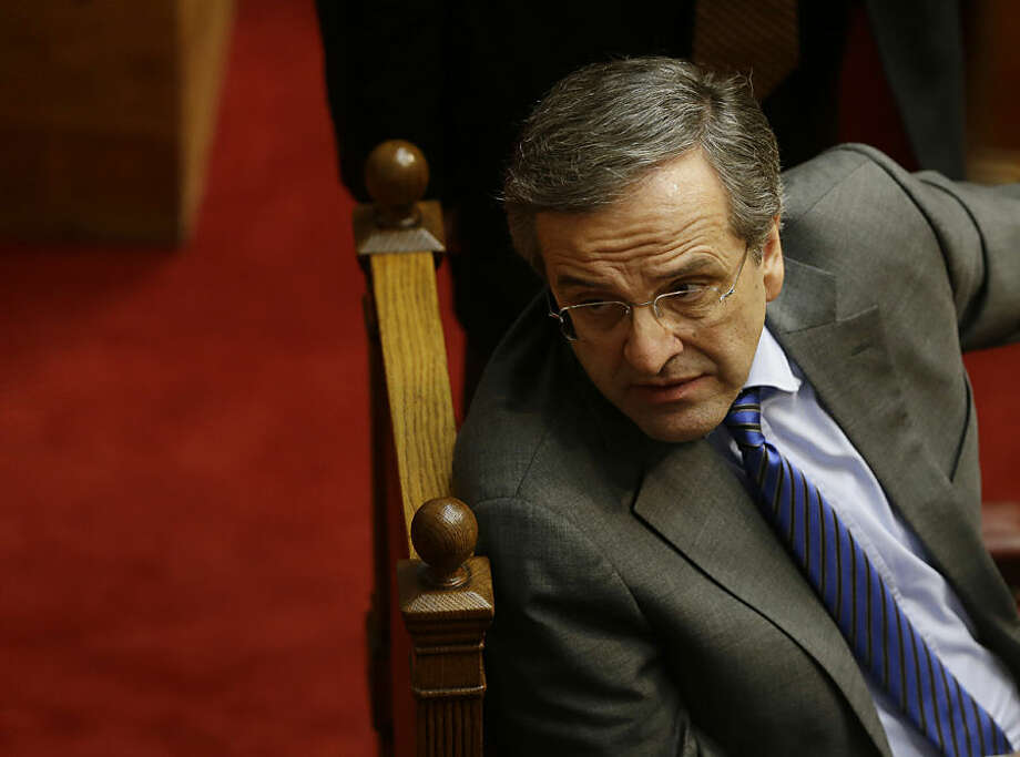 Greece's Prime Minister Antonis Samaras looks over his shoulder as he attends the second round of voting to elect a new Greek president at the Parliament in Athens on Tuesday, Dec. 23, 2014. Greek lawmakers have failed to elect the country's new president in a second round of voting, leaving the government with a final attempt next week to break an impasse that could force early elections. The conservative-led government's candidate, Stavros Dimas, received 168 votes in Tuesday's ballot, far short of the 200 needed for his election. (AP Photo/Thanassis Stavrakis)
