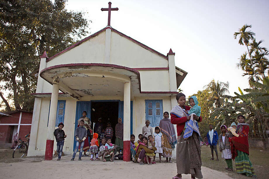 Indian tribal settlers take refuge in a local church after their village was attacked by an indigenous separatist group called the National Democratic Front of Bodoland, in Shamukjuli village in Sonitpur district of Indian eastern state of Assam, Wednesday, Dec. 24, 2014. Hundreds of survivors of a brutal rebel attack that killed at least 63 people in northeastern India sought shelter Wednesday in a church and school while security forces imposed a curfew in a bid to contain the latest bout of ethnic violence. (AP Photo/Anupam Nath)