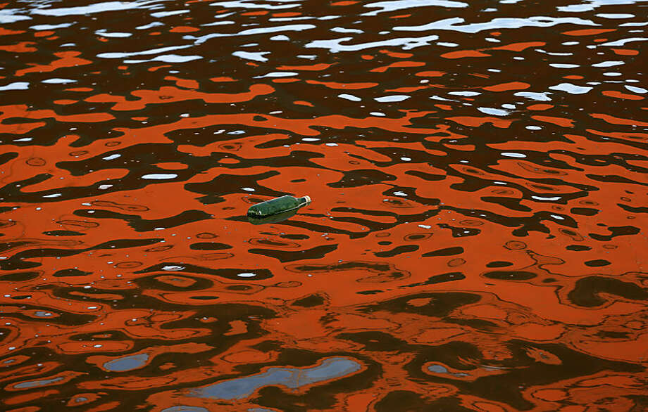 A bottle floats on reflection of a bridge on the Sava river, in Belgrade, Serbia, Tuesday, Dec. 23, 2014. Unusually warm weather for this time of the year is predicted for upcoming days in Serbia. (AP Photo/Darko Vojinovic)