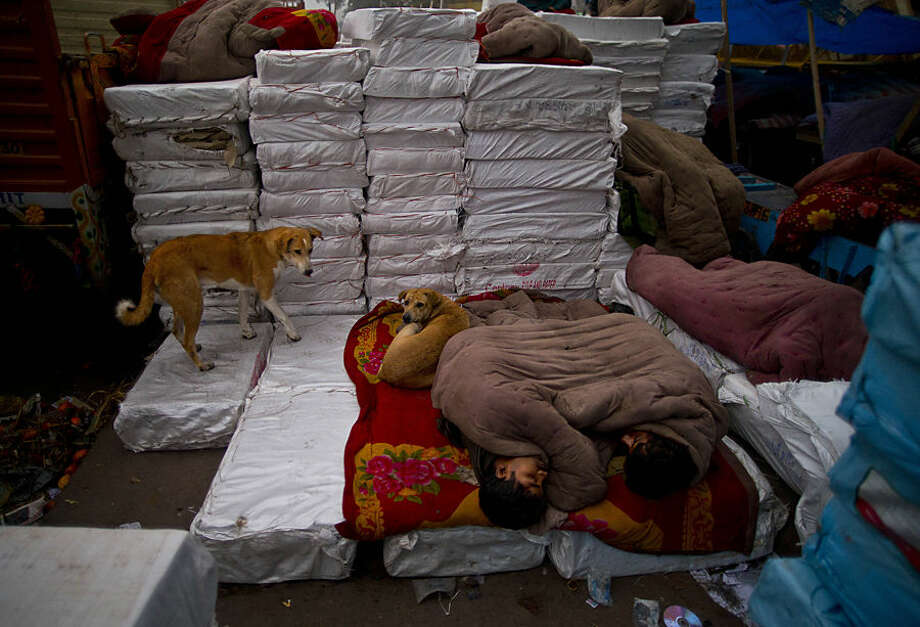Indian laborers sleep on makeshift beds by the roadside on a cold morning in New Delhi, India, Tuesday, Dec. 23, 2014. Intense cold coupled with thick blanket of fog has engulfed most parts of north India throwing normal life out of gear and disrupting rail, road and air traffic. (AP Photo/Saurabh Das)