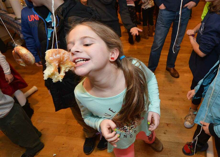 Nomi Friedman, 9, nibbles on a snack as children try to eat donuts swinging on strings during the Wilton Community Hanukkah Party at Ambler Farm.