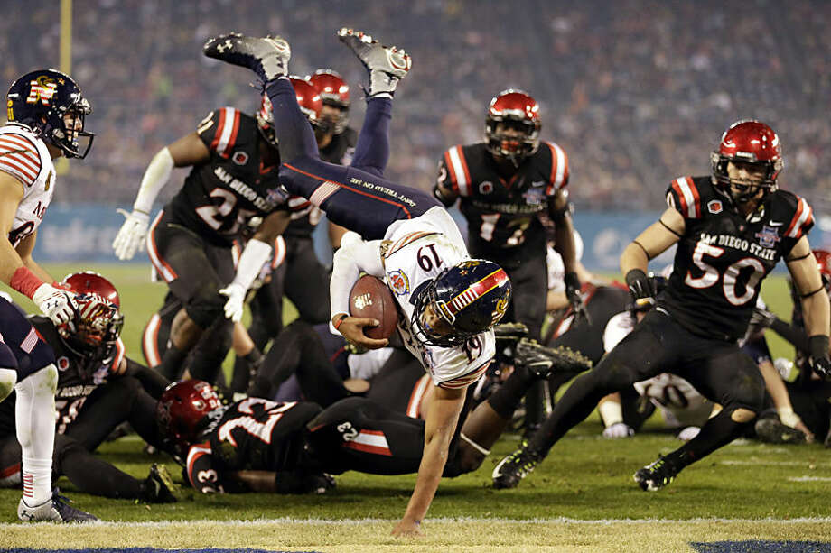 Navy quarterback Keenan Reynolds (19) jumps into the end zone for a touchdown against San Diego State during the second half of the Poinsettia Bowl NCAA college football game Tuesday, Dec. 23, 2014, in San Diego. Navy won 17-16. (AP Photo/Gregory Bull)