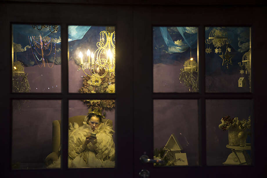 A street entertainer holds her cell phone in a pavilion during a minute of rest in a pavilion in downtown Moscow decorated for the New Year and Christmas, Russia, Tuesday, Dec. 23, 2014. (AP Photo/Alexander Zemlianichenko)