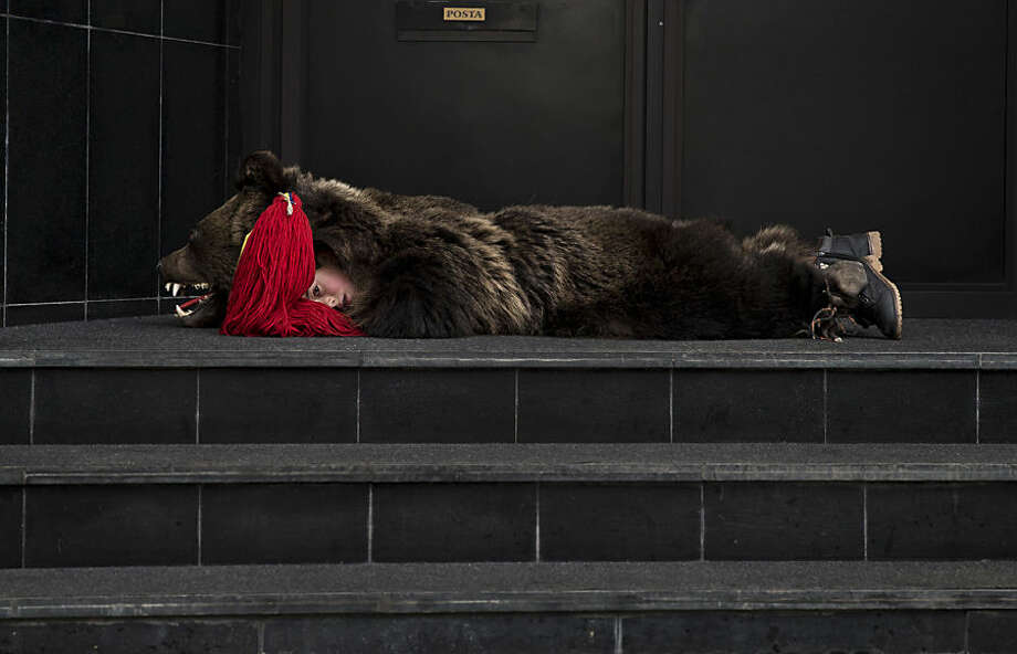 A child from from Dofteana, northern Romania wearing a bear fur, lies on an office building's steps while taking a break from performing a holiday season ritual in Bucharest, Romania, Tuesday, Dec. 23, 2014. In pre-Christian rural traditions, dancers wearing colored costumes or animal furs, tour house to house in villages singing and dancing to ward off evil. In recent years following the economic downturn in Romania, a European Union member since 2007, the tradition has moved to Romania's cities where dancers travel to perform the ritual for money during the Christmas and New Year's period. (AP Photo/Vadim Ghirda)