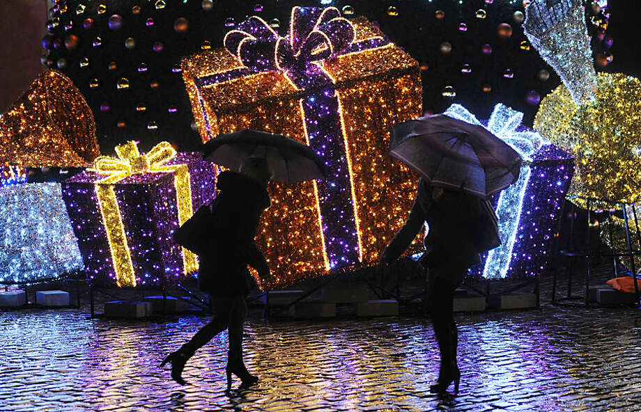 People walk past Seasonal decorations on a rainy evening in Warsaw, Poland, Tuesday, Dec. 23, 2014, one day ahead of Christmas Eve. Weather forecasts predict a rainy Christmas in Poland. (AP Photo / Alik Keplicz)