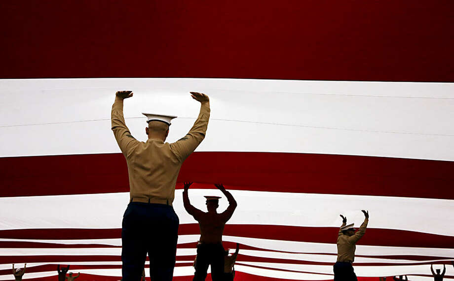 Marines hold up a U.S. flag before Navy played San Diego State in the Poinsettia Bowl NCAA college football game Tuesday, Dec. 23, 2014, in San Diego. (AP Photo/Gregory Bull)