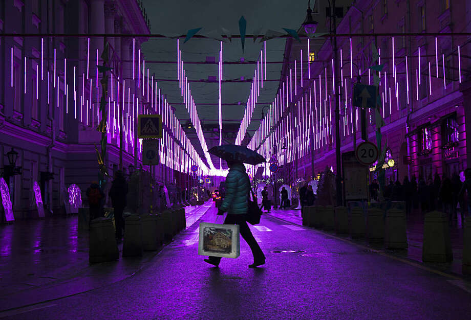 A woman crosses a street decorated with New Year and Christmas illumination in the center of Moscow, Russia, Tuesday, Dec. 23, 2014. (AP Photo/Alexander Zemlianichenko)